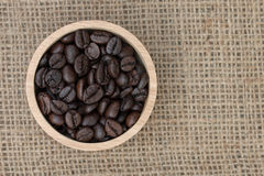 Top view : Coffee beans in wooden cup on sack texture background Royalty Free Stock Images