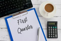 Top view of coffee,calculator,keyboard,pen,clipboard,and paper written with First Quarter. Growth report investment business information financial profit result stock photography