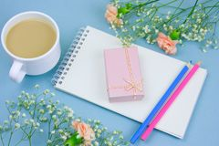 Coffee with cream cup, notebook,pencils and pink gift box with flowers frame on a blue background. Top view coffee with cream cup, notebook,pencils and pink gift stock photo