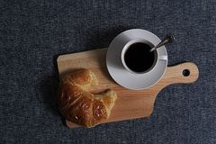 Top view of Coffee and croissant. A cup of coffee and croissant on wooden board in blue background Stock Images