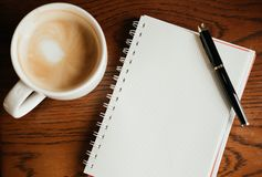 Top view. coffee cup with coffee. pen putting on blank notebook. Have wooden table are background. image for beverage,business,education,business accessory Royalty Free Stock Images