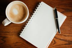 Top view. coffee cup with coffee. pen putting on blank notebook. Have wooden table are background. image for beverage,business,education,business accessory Royalty Free Stock Photos