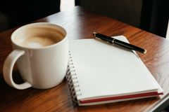 Top view. coffee cup with coffee. pen putting on blank notebook. Have wooden table are background. image for beverage,business,education,business accessory Royalty Free Stock Image