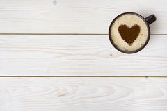 Top view of coffee cup with heart on wooden background Royalty Free Stock Photo