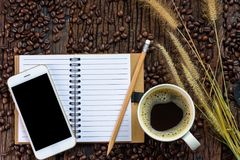 Top view of coffee cup, notebook, pencil, dry grass flower, coffee beans and smartphone with black blank screen on wooden table ba Royalty Free Stock Photo