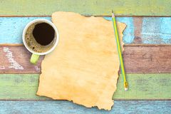 Top view coffee cup,pencil and old paper on office wooden table. Space for use and design Royalty Free Stock Image