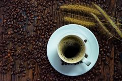 Top view of coffee cup on saucer with grass flowers and roasted coffee beans on wooden table Stock Photography
