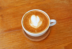 Top view of a coffee with heart pattern in a white cup on wooden background. Latte art Stock Image