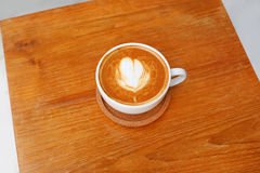 Top view of a coffee with heart pattern in a white cup on wooden background. Latte art Royalty Free Stock Photography