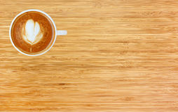 Top view of a coffee with heart pattern in a white cup on wooden background. Latte art Stock Images