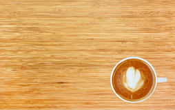 Top view of a coffee with heart pattern in a white cup on wooden background. Latte art Stock Photography