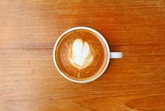 Top view of a coffee with heart pattern in a white cup on wooden background. Latte art Royalty Free Stock Photo