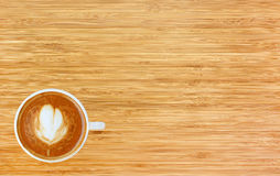 Top view of a coffee with heart pattern in a white cup on wooden background. Latte art Royalty Free Stock Photos