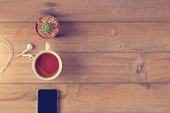 Top view of coffee, mobile phone and cactus on a wooden background Stock Photos