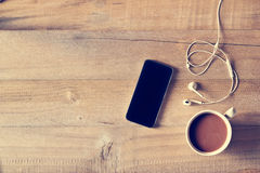 Top view of coffee, mobile phone on a wooden background Stock Photography