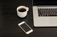 Top view of coffee mug, smartphone and laptop keyboard, black table Stock Photos