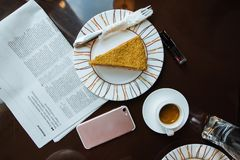 Top view Coffee served with cake, newspapper an cellphone on the dark brown table stock photos