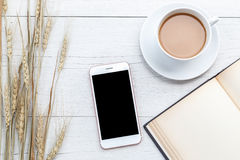 Top view coffee, smartphone and empty book on white wooden table Stock Photos