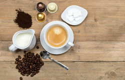 Top view of coffee table. On rustic wooden background :White porcelain cup of creamy mocha coffee with fresh roasted and grinded coffee beans, jug of milk Stock Images