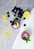 Top view of cold drinks with mint and berries. Berry shots on an ice background. Healthy blackberries and cut lemons. Stock Photography