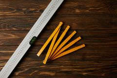 Top view of collapsible meter and spirit level on wooden table royalty free stock photo