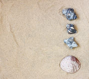 Top view of collection of beach stones rock and shells over sand. Stock Image