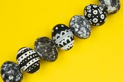 Collection of dyed black and white easter eggs on a yellow background. Top view collection of dyed black and white easter eggs on a yellow background royalty free stock photos