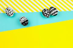 Collection of dyed black and white easter eggs on a yellow and blue background. Top view collection of dyed black and white easter eggs on a yellow and blue royalty free stock images