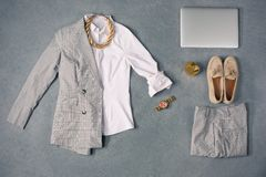 The collection of elegant clothes. The top view of collection of elegant female clothes on gray - suit, pants, shoes, laptop Royalty Free Stock Images