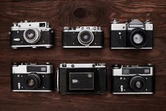 Top view of the collection of retro cameras over wooden backgrou Stock Photos