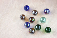 Top view of collection of shiny marbles on wooden background Royalty Free Stock Photos