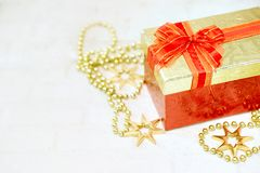 Top view color gift box with ribbon on white wooden plank background. Top view red gift box with golden ribbon on white brick plank background with golden stock image