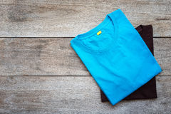 Top view of color T-Shirt on grey wood plank Royalty Free Stock Images