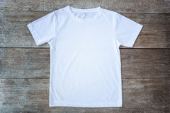 Top view of color T-Shirt on grey wood plank. Background Stock Photos