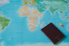 Top view. color world map with small pin and passport placed on. Top view. color world map with small pin and passport book placed on them. this image for Stock Photography
