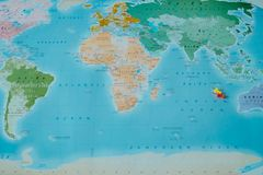 Top view. color world map with small pin placed on them. this im. Top view. color world map with small pin red and yellow placed on them. this image for Stock Photo