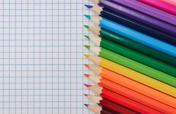 Top view of colored pencils on the grid notepad royalty free stock image