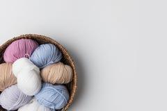 Colored yarn balls in wicker basket on white background. Top view of colored yarn balls in wicker basket on white background Royalty Free Stock Photos