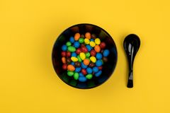 Colorful Candies in a bowl. Top view of colorful candies in a black bowl with the black spoon on the yellow table Royalty Free Stock Photos