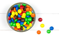 Top-view of colorful candies in a bowl. On white wooden surface Stock Image