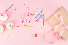 Top view of colorful candles, tasty birthday cupcakes and gift box on pink Royalty Free Stock Photo