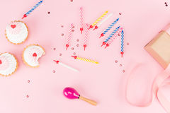 Top view of colorful candles, tasty birthday cupcakes and gift box on pink Royalty Free Stock Images