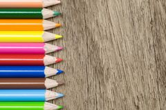 Top view of colorful color pencil stacked on wood background. Id Stock Image