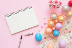 Top view colorful easter egg painted in pastel colors composition and mock up blank notebook with paint brush on pink pastel. Flat lay top view colorful easter Royalty Free Stock Images
