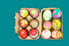 Top view of colorful easter egg in pulp box on green background Stock Photography