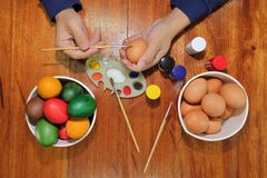 Top view of colorful Easter eggs are being painted with paintbrush and palette by young man on wooden table. Stock Images