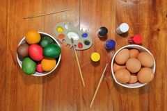 Top view of colorful eggs with a paintbrush and palette are preparing for Happy easter day. Royalty Free Stock Photo