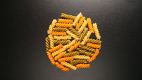 TOP VIEW: Colorful fusilli pastas on a black table Stock Image