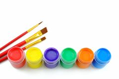 Top view of colorful gouache paints and three red paintbrushes. Stock Photo