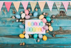 top view of colorful happy easter greeting card with colorful eggs around on blue stock photos